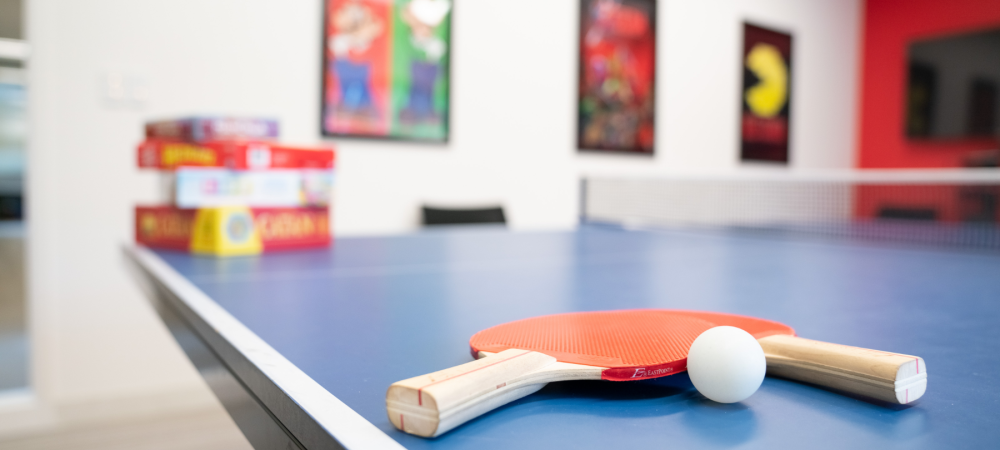Image of paddles and a ball on a ping pong table in a game room