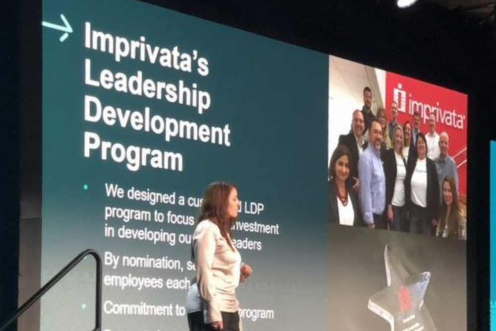 Image of an employee giving a presentation with slides on Imprivata's leadership development program behind her
