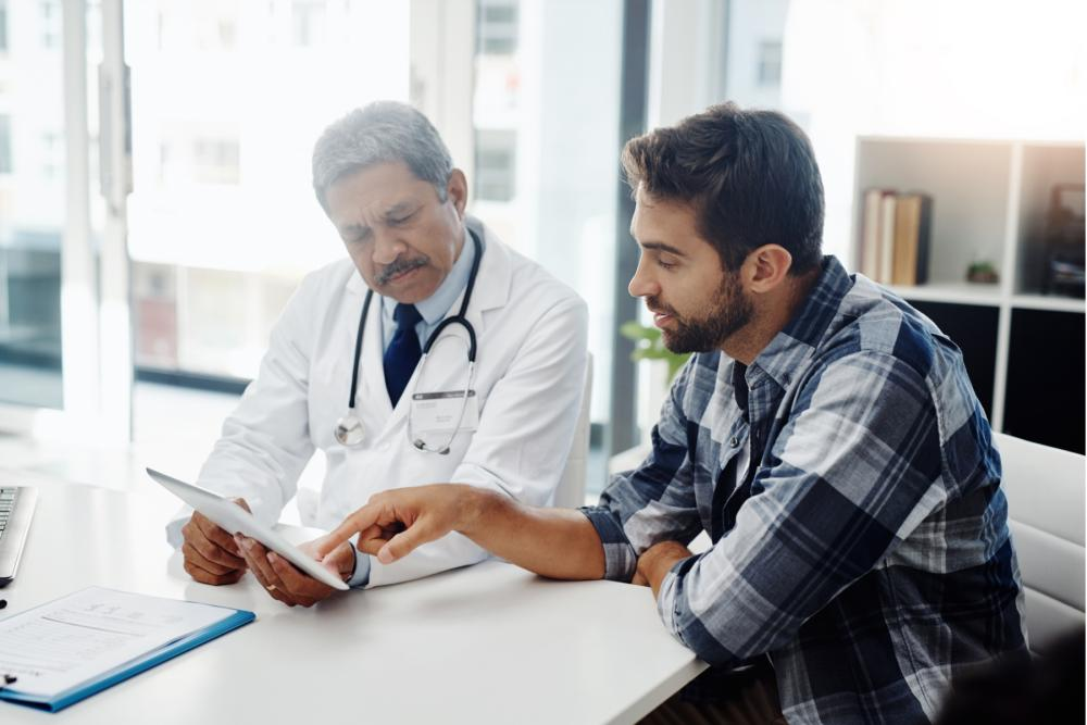 Image of a doctor and a man looking at a smart tablet together